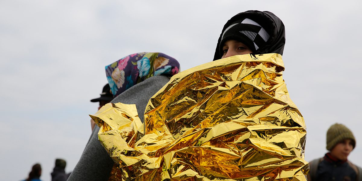 Woman covered with emergency blanket after her arrival in Greece.