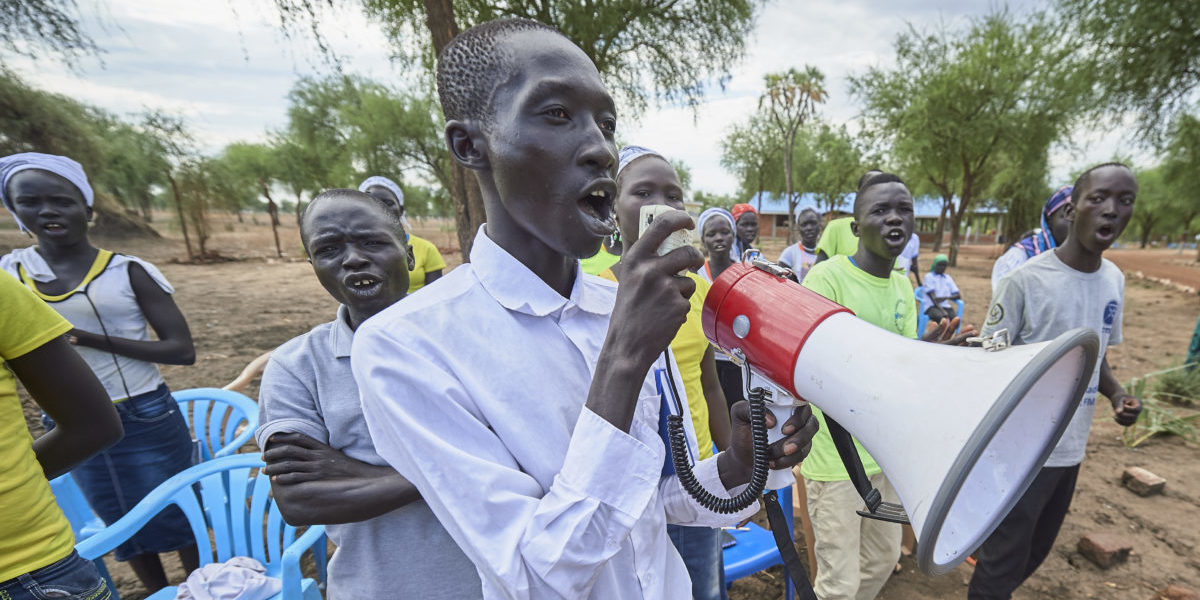 Using a megaphone, a man leads a group of refugees in song during an activity sponsored by JRS in the Doro Refugee Camp in Maban, South Sudan.